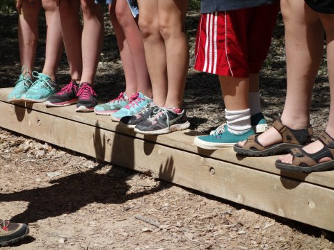 Feet of several children, balancing on a board together