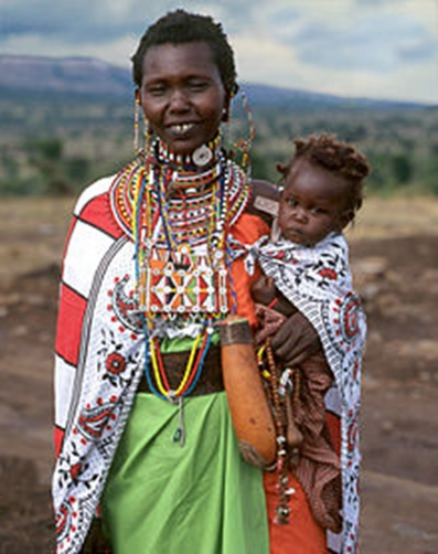 A modern-day Maasai mother dressed up in her finest. Notice the bare ground and sparse vegetation behind her. Photo by David Zarembka