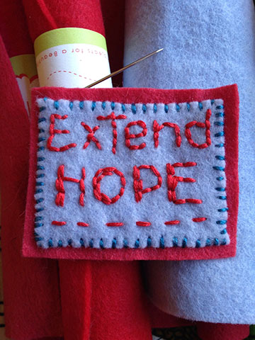 "Felt patch embroidered with the words, ""Extend hope."""
